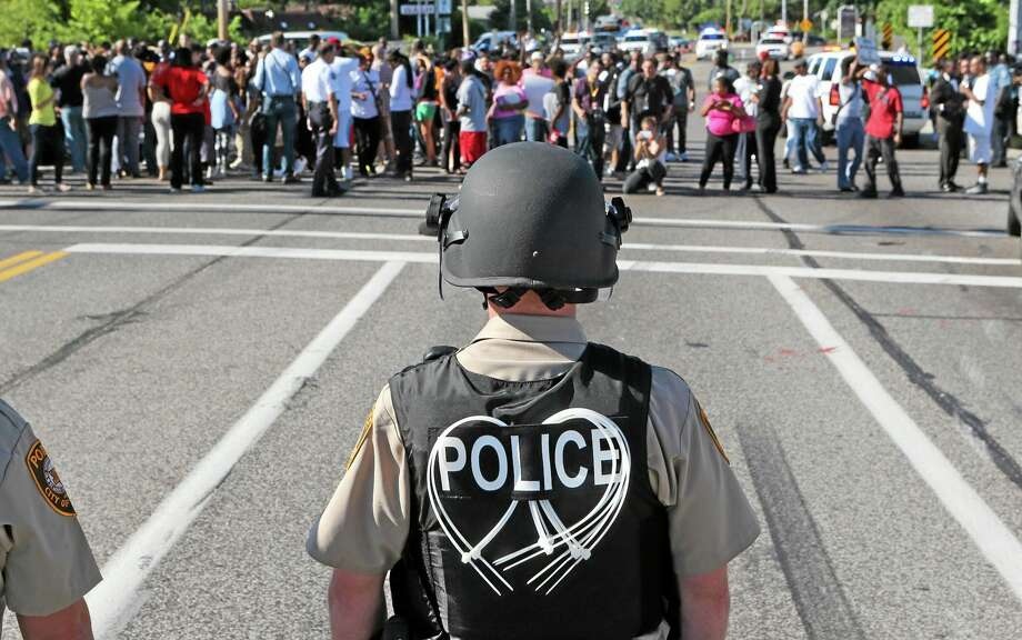 A line of police wait for demostrators at Canfield Avenue after they had walked down W. Florissant in Ferguson, Mo. on Wednesday, Aug. 13, 2014. On Saturday, Aug. 9, 2014, a white police officer fatally shot Michael Brown, an unarmed black teenager, in the St. Louis suburb. Photo: (AP Photo/St. Louis Post-Dispatch, J.B. Forbes) / St. Louis Post-Dispatch