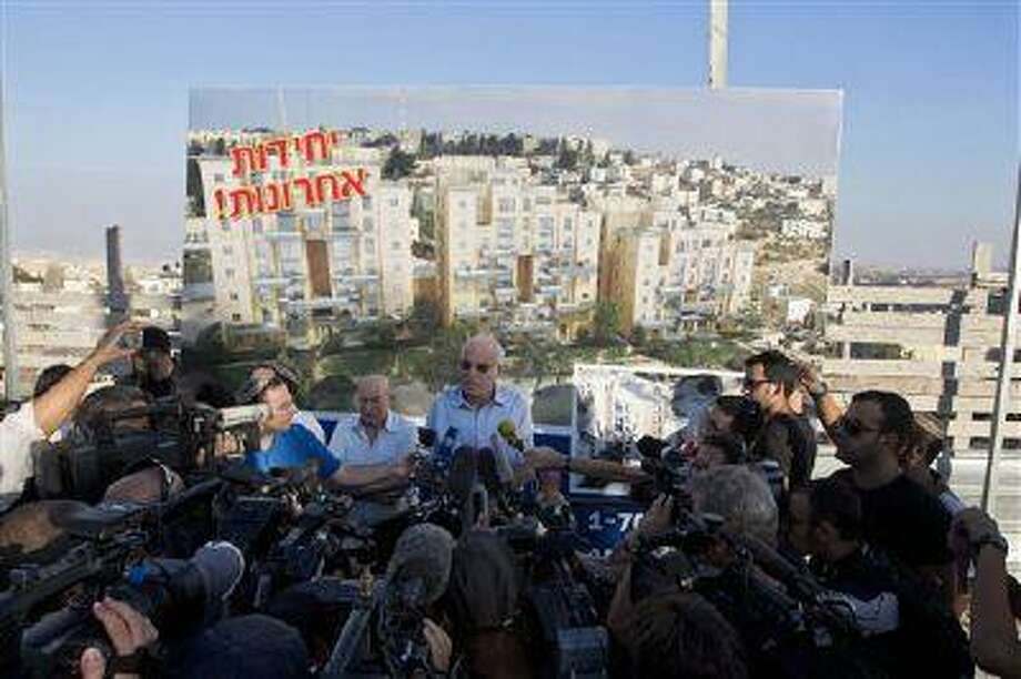 Israeli Minister of Housing and Construction Uri Ariel, center, speaks to journalists during a ceremony to mark the resumption of the construction of housing units in an east Jerusalem neighborhood Aug. 11. Photo: AP / AP