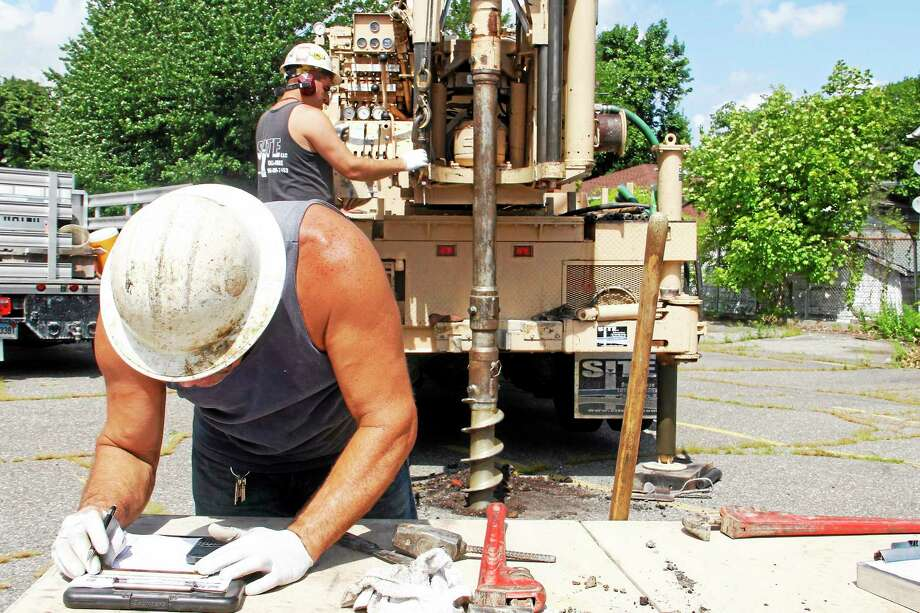 John DeAngelis Jr. takes notes as his son, John DeAngelis III, operates an auger  behind him at the parking lot on Field Street on Monday, July 28 in Torrington. The two were drilling holes to collect soil samples to help with the design of the Litchfield County Courthouse complex. Photo: Esteban L. Hernandez-Register Citizen