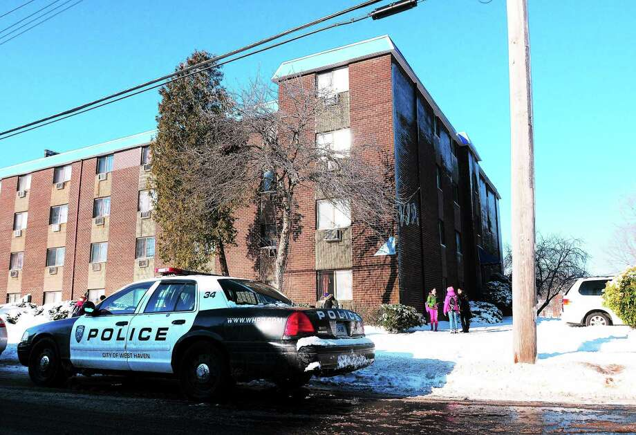 A West Haven police cruiser can be seen outside the apartment building on Canton Street where a woman suffered burns after her estranged husband allegedly threw hot oil on her early Wednesday morning. Photo: Arnold Gold — New Haven Register