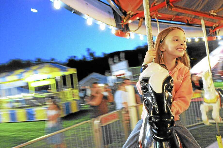 Mariah Walker, 7, of Winsted, rides the carousel at the 2013 Fireman's Carnival. Photo: Laurie Gaboardi — The Register Citizen