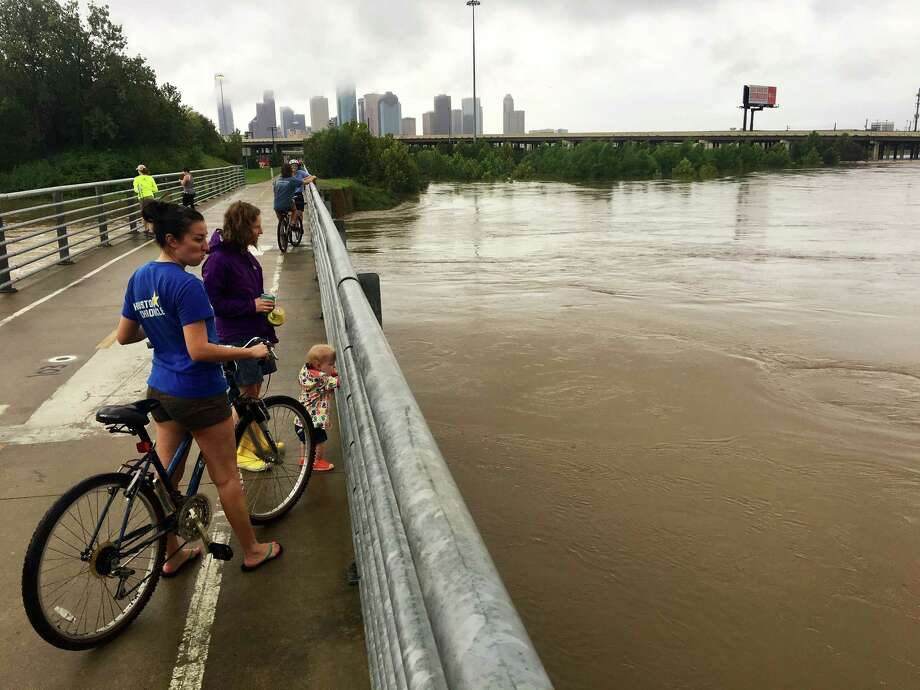 People take advantage of a lull in the rains from Tropical Storm Harvey to check out White Oak Bayou from a bike path in the Heights. Photo: Jill Karnicki / Houston Chronicle