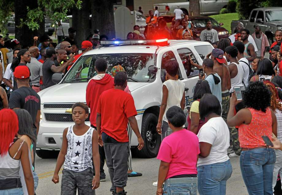 Protesters bang on the side of a police car Sunday evening, Aug. 10, 2014, in Ferguson, Mo. A few thousand people have crammed the street where a black man was shot multiple times by a suburban St. Louis police officer. The candlelight vigil Sunday night was for 18-year-old Michael Brown, who died a day earlier. Police say he was unarmed. Photo: (AP Photo/St. Louis Post-Dispatch, J.B. Forbes)   / St. Louis Post-Dispatch