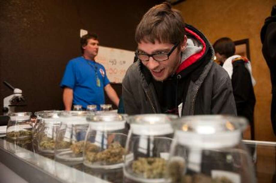 DENVER, CO - JANUARY 1:  Tyler Williams of Blanchester, Ohio selects marijuana strains to purchase at the 3-D Denver Discrete Dispensary on January 1, 2014 in Denver, Colorado. Legalization of recreational marijuana sales in the state went into effect at 8am this morning.  (Photo by Theo Stroomer/Getty Images) Photo: Getty Images / 2014 Getty Images
