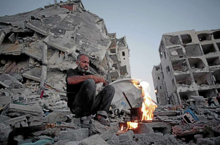 Palestinian Ziad Rizk, 38, makes coffee  next to one of the destroyed Nada Towers, where he lost his apartment and clothes shop, in the town of Beit Lahiya, northern Gaza Strip, Monday, Aug. 11, 2014. (AP Photo/Khalil Hamra) Photo: AP / AP