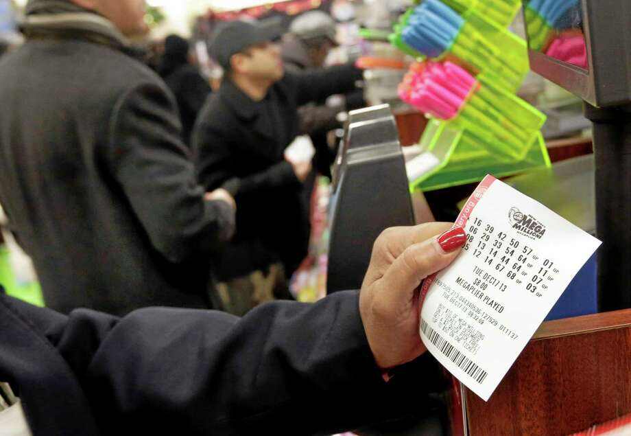 A woman plays the Mega Millions lottery at a shop in New York's Penn Station, Tuesday, Dec. 17, 2013. The Mega Millions jackpot soared to $586 million on Monday, still short of the $656 million U.S. record set in a March 2012 drawing.  (AP Photo/Richard Drew) Photo: AP / AP