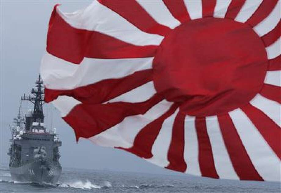"""Japan Maritime Self-Defense Force escort ship """"Kurama,"""" left, navigates behind destroyer """"Yudachi,"""" with a flag, during a 2012 fleet review in water off Sagami Bay, south of Tokyo. Japan has released a near-final draft of its first national security strategy that calls for a stronger military amid the rise of China. Photo: AP / AP"""