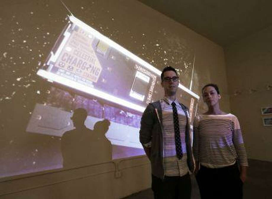 Jon Gibson and Amanda White pose with a projected image of their artwork that will be launched into space, at their studio in the Echo Park district of Los Angeles Wednesday, July 31, 2013. Photo: AP / AP