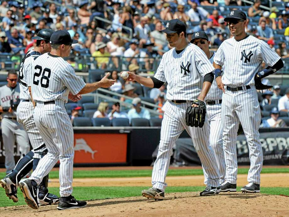 Yankees pitcher Hiroki Kuroda, right, hands the ball to manager Joe Girardi as he leaves the game during the fifth inning Saturday. Photo: Bill Kostroun — The Associated Press  / FR51951 AP