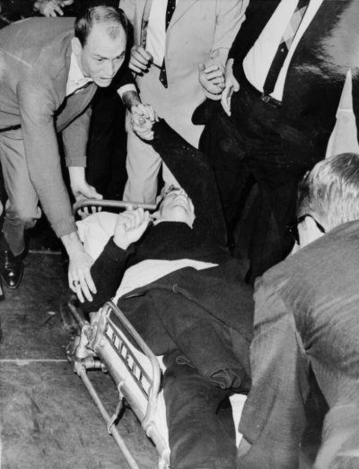 President John F. Kennedy's alleged assassin Lee Harvey Oswald is hurried into an ambulance after being shot at Dallas City Prison by night club owner Jack Ruby. Photo: Getty Images / Hulton Archive