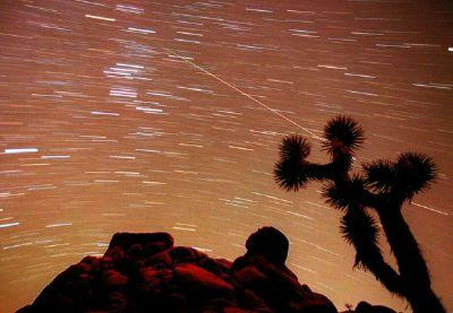 A meteor streaks through the sky over Joshua trees and rocks at Joshua Tree National Park in Southern California's Mojave Desert in this 30-minute time exposure ending at 1:15 a.m. PST Tuesday, Nov. 17, 1998. Photo: AP / AP