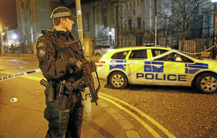 A police officer secures the area close to a small explosion in the Cathedral Quarter in Belfast city centre, Northern Ireland, Friday, Dec. 13, 2013.  Police have evacuated the area which is one of the main entertainment venues in Belfast with many bars and restaurants.  It is  widely believed to have been planted  by Irish Republican dissident terrorists.   (AP Photo/Peter Morrison) Photo: AP / AP