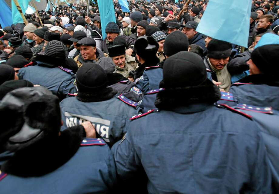 In this photo taken Wednesday, Feb. 26, 2014, Crimean Tatars clash with police in front of a local government building in Simferopol, Crimea, Ukraine. The arrival of Russian troops in Crimea has opened old wounds among the Crimean Tatars, who have rallied to support the new Ukrainian leaders in Kiev and fear this will make them a target of rising Russian nationalism on the Black Sea peninsula. (AP Photo/Darko Vojinovic) Photo: AP / AP