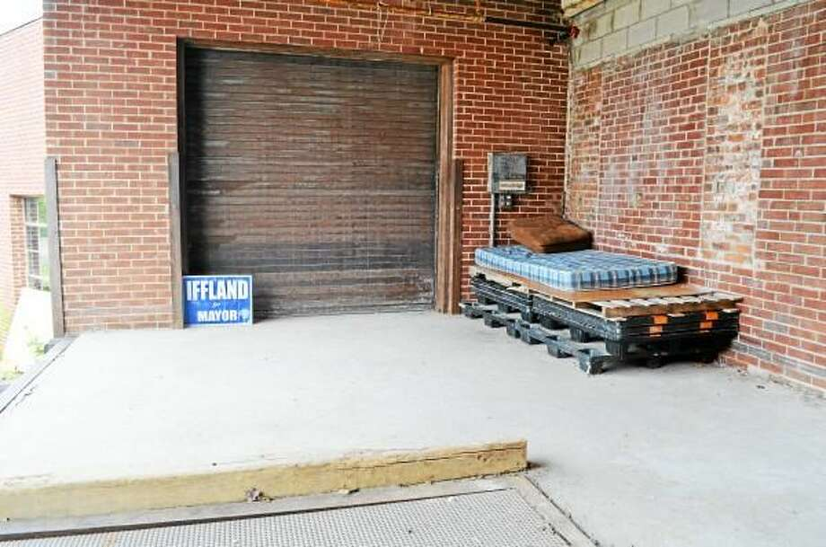 An abandoned mattress and cushion set up on a loading dock at the uninhabitted former Register Citizen building in Torrington is an apparent make-shift bed. John Berry - Register Citizen