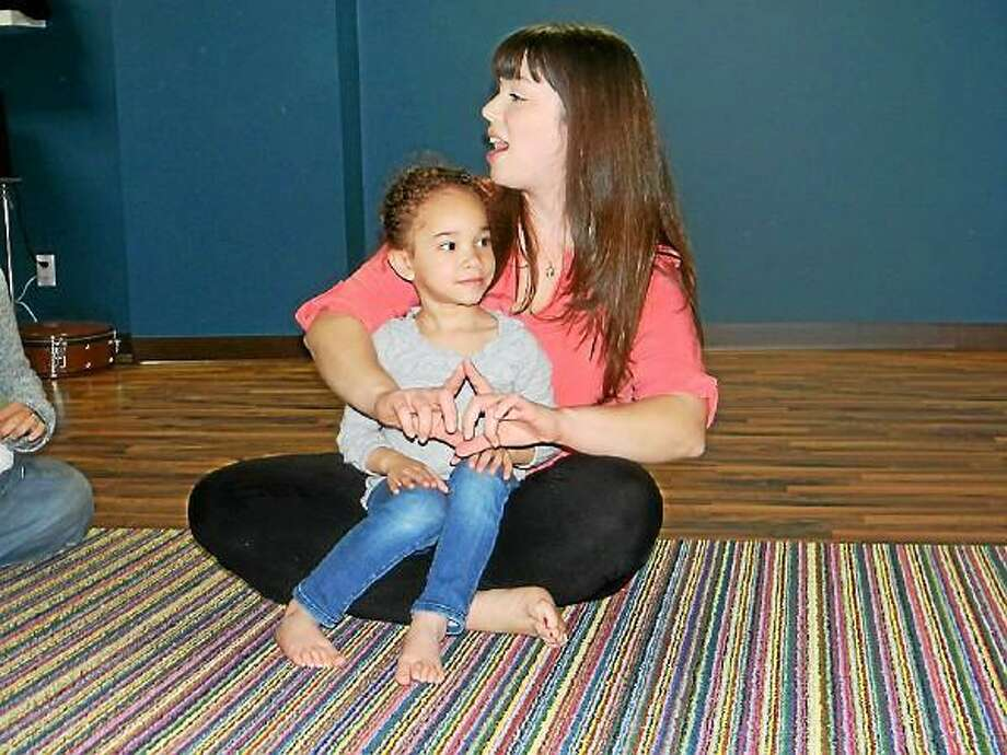 Center director and teacher Leslie Pratt sings with a girl during a Music Together class, a music and movement development program for children opening classes in Litchfield in September. (Submitted photo)