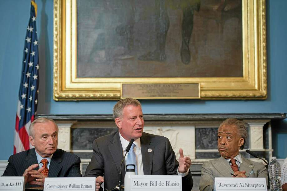 "FILE- In this July 31, 2014 file photo provided by the New York City Mayoral Photography Office, New York Mayor Bill de Blasio, center, is seated between New York City Police Commissioner William Bratton, left, and the Rev. Al Sharpton, during a round table discussion convened to ease tensions over the July 17, police involved death of Eric Garner. In an interview with The Associated Press, Police Commissioner Bill Bratton said he wanted to counter ""some of the misimpressions and some of the momentum that's been gained by self-serving interests"" in the wake of the videotaped death last month of Garner. (AP Photo/New York City Mayoral Photography Office, Bob Bennett, File) Photo: AP / New York City Mayoral Photography Office"
