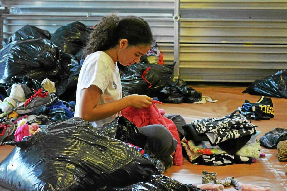 One of the volunteers at the annual Junior Dress for Success event put on by Torrington Early Childhood Collaborative sorts through donated clothes and folds them before dispersing them to the tables arranged by size. Photo: Jenny Golfin - Register Citizen