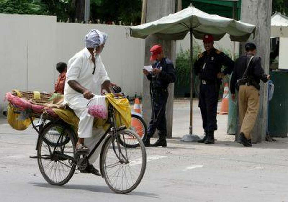 A Pakistani vendor rides his bicycle past the U.S. Consulate in Lahore, Pakistan, Aug. 9. Photo: ASSOCIATED PRESS / AP2013
