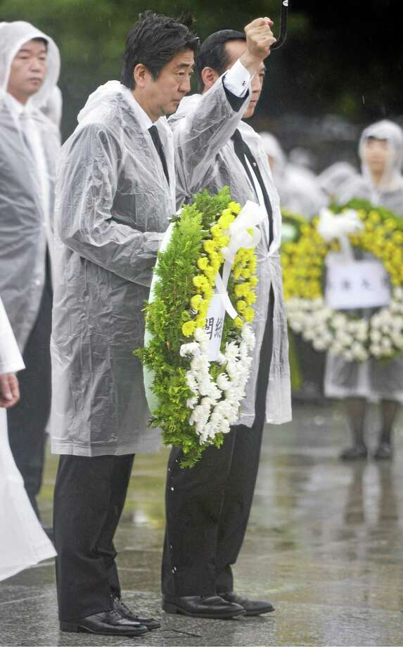Japan's Prime Minister Shinzo Abe, center left, offers flowers to the atomic bomb victims during a ceremony at the Hiroshima Peace Memorial Park in Hiroshima, western Japan, Wednesday, Aug. 6, 2014. Japan marked the 69th anniversary Wednesday of the atomic bombing of Hiroshima. (AP Photo/Kyodo News) JAPAN OUT, MANDATORY CREDIT Photo: AP / Kyodo News