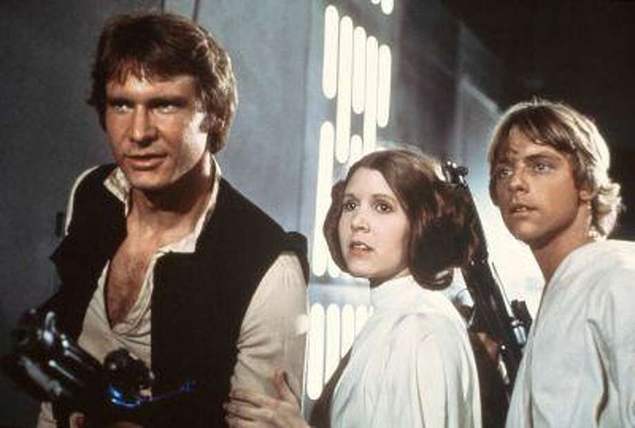 "FILE - This 1977 file image provided by 20th Century-Fox Film Corporation ahows, from left, Harrison Ford, Carrie Fisher, and Mark Hamill in a scene from ""Star Wars"" movie released by 20th Century-Fox in 1977. Having recently purchased the ""Star Wars"" franchise from Lucasfilm for $4 billion, the Walt Disney Co. is shifting the films into hyperdrive. Not only has Disney already begun working on a new trilogy, to start with J.J. Abrams directing episode seven, but reports this week have said possible spinoffs are being developed for young Han Solo, the bounty hunter Boba Fett and Yoda. (AP Photo/20th Century-Fox Film Corporation) Photo: ASSOCIATED PRESS / A1977"