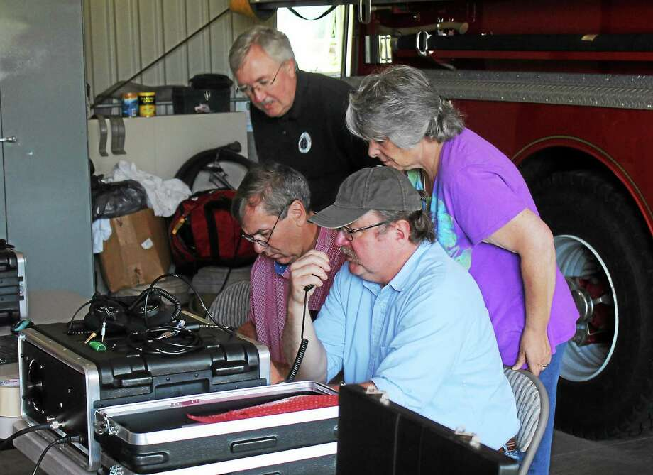 Region 5 ARES members Tim Angel, top left, Sandy Wilcox top right, Dave Wilcox, right, and Paul Gibb, left, test out the group's equipment Saturday in the fire station located in the Winchester Grange hall building. Photo: John Nestor — Special To The Register Citizen