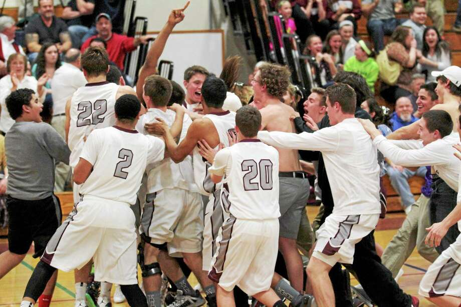 The Farmington Indians rush the court following Obi Momah's game-winning 3-pointer at the buzzer. Photo: Marianne Killackey — Special To Register Citizen  / 2013