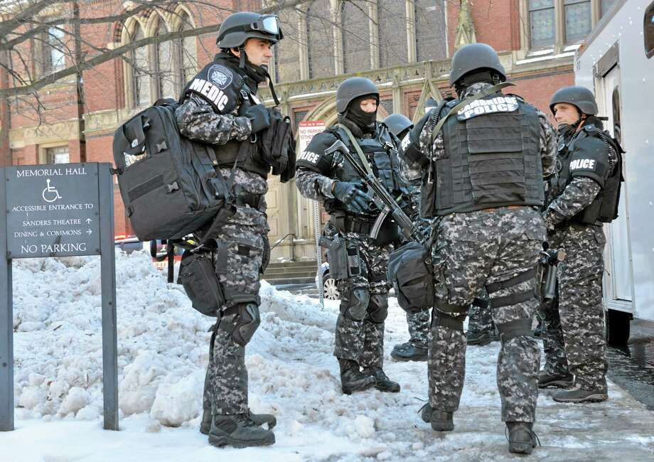 Tactical police assemble outside a building at Harvard University in Cambridge, Mass., Monday, Dec. 16, 2013. Four buildings on campus were evacuated after campus police received an unconfirmed report that explosives may have been placed inside, interrupting final exams. (AP Photo/Josh Reynolds) Photo: AP / AP