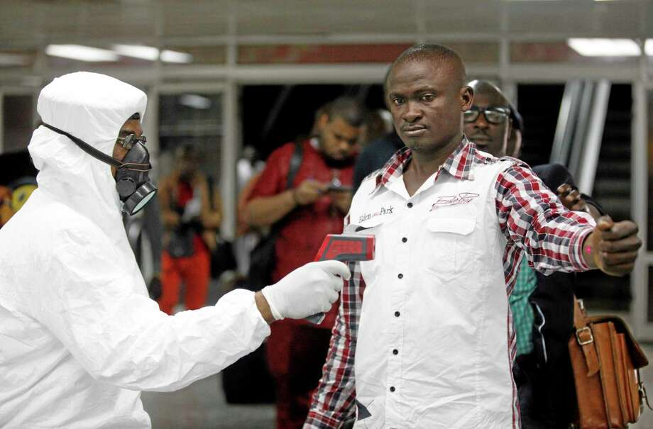 FILE - In this Aug. 6, 2014 file photo, a Nigerian port health official uses a thermometer on a worker at the arrivals hall of Murtala Muhammed International Airport in Lagos, Nigeria. As the Ebola outbreak in West Africa grows, airlines around the globe are closely monitoring the situation but have yet to make any drastic changes. (AP Photo/Sunday Alamba, File) Photo: AP / AP