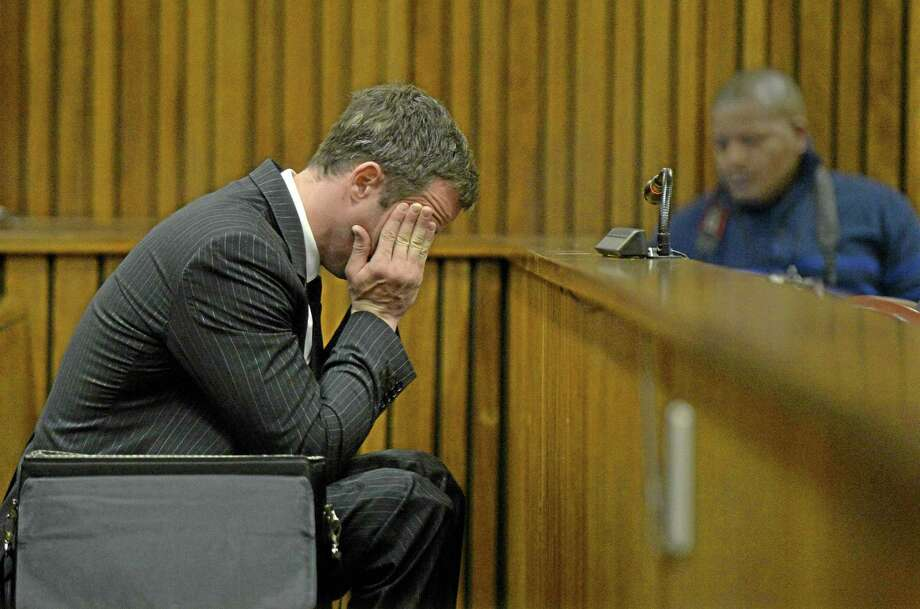 Oscar Pistorius, gestures, as he sits in court, during his trial in Pretoria, South Africa, Friday, Aug. 8, 2014. The chief defense lawyer for Oscar Pistorius delivered final arguments in the athlete's murder trial on Friday, alleging that Pistorius thought he was in danger when he killed girlfriend Reeva Steenkamp and also that police mishandled evidence at the house where the shooting happened.(AP Photo/Herman Verwey, Pool) Photo: AP / POOL MEDIA 24