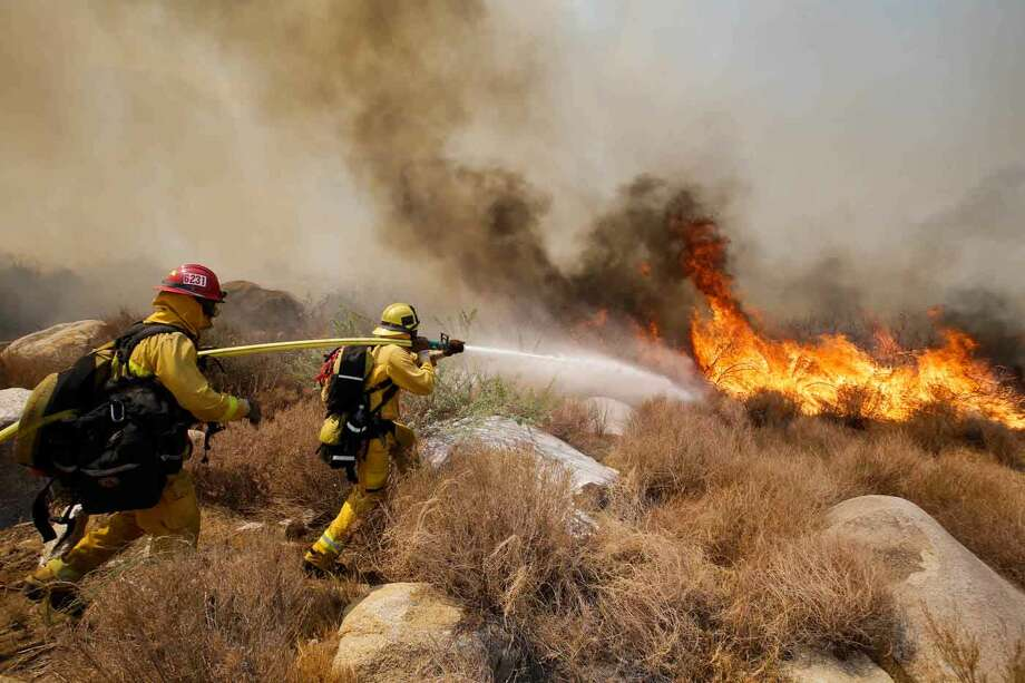 Firefighters battle a wildfire, Thursday, Aug. 8, 2013, in Cabazon, Calif. About 1,500 people have fled and three are injured as a wildfire in the Southern California mountains quickly spreads. Several small communities have evacuated. (AP Photo/Jae C. Hong) Photo: ASSOCIATED PRESS / AP2013
