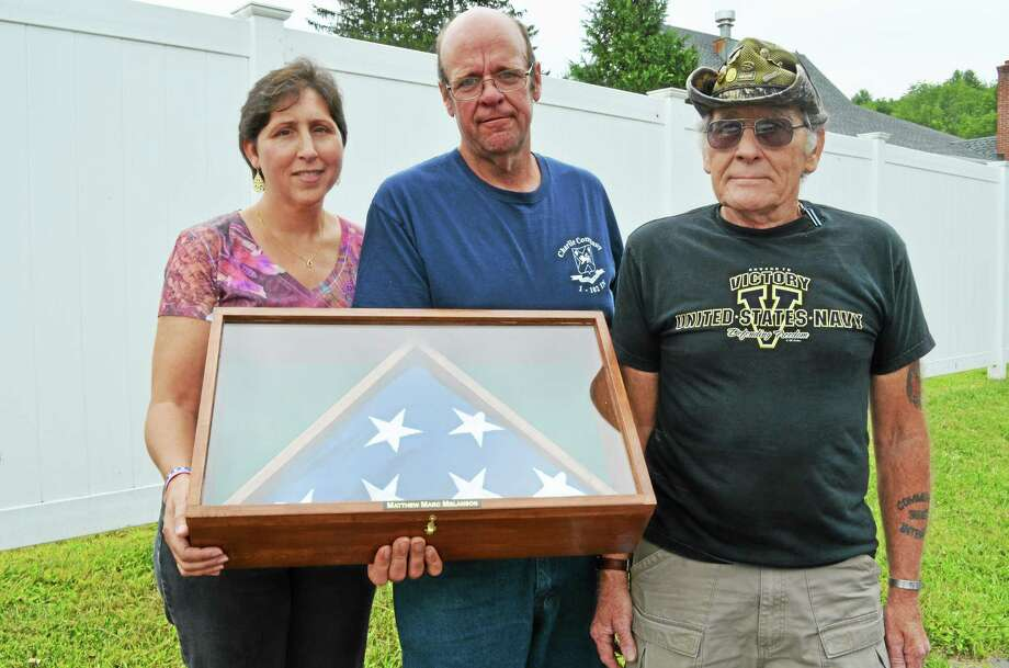 Tracy and Marc Melanson hold the flag that was presented to them by Art Melycher, right, following the 2013 Matthew Marc Melanson Memorial Ride in Winsted. Photo: Register Citizen File Photo