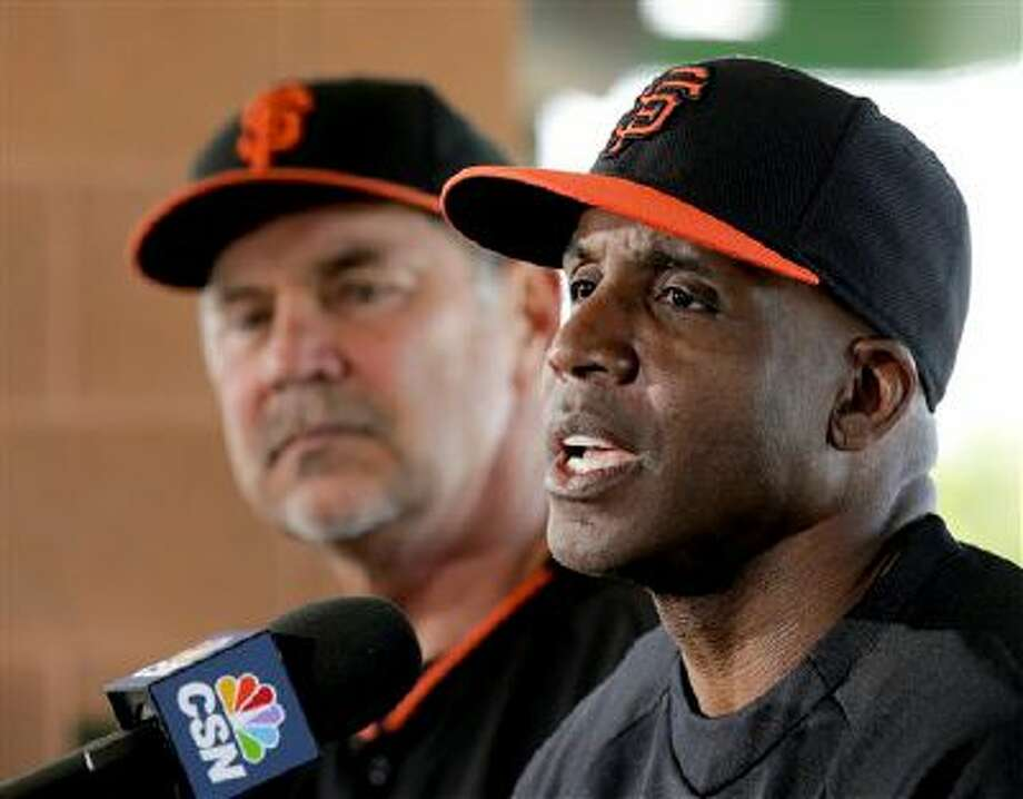 San Francisco Giants manager Bruce Bochy, left, listens as former player Barry Bonds speaks during a news conference before a spring training baseball game in Scottsdale, Ariz., Monday, March 10, 2014. Bonds starts a seven day coaching stint today. (AP Photo/Chris Carlson) Photo: AP / AP