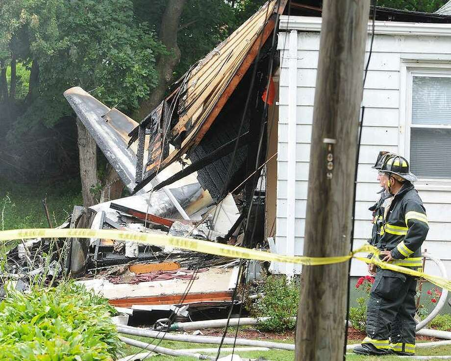 Photos by Peter Hvizdak Ñ RegisterPlane crash that hit two houses at 64 and 68 Charter Oak Avenue between James and Gordon Streets in East Haven, Connecticut Friday afternoon, August 9. 2013. Photo: New Haven Register / ©Peter Hvizdak /  New Haven Register