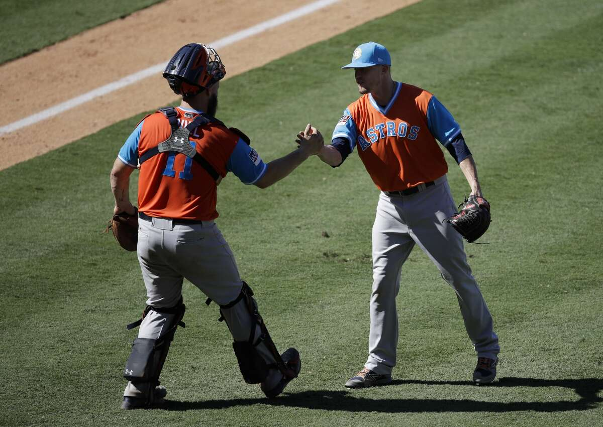 Houston Astros relief pitcher Ken Giles, right, and catcher Evan Gattis shake hands after their team's 7-5 win against the Los Angeles Angels in a baseball game, Sunday, Aug. 27, 2017, in Anaheim, Calif. (AP Photo/Jae C. Hong)