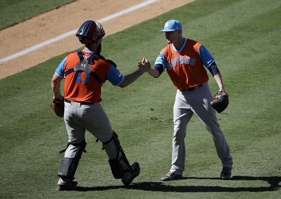 Houston Astros relief pitcher Ken Giles, right, and catcher Evan Gattis shake hands after their team's 7-5 win against the Los Angeles Angels in a baseball game, Sunday, Aug. 27, 2017, in Anaheim, Calif. (AP Photo/Jae C. Hong) Photo: Jae C. Hong/Associated Press