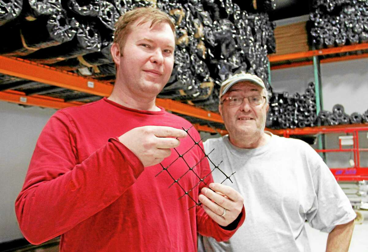 Doug Korfel, left, stands next to his father, John, as he holds up a piece of fencing material sold by Critterfence, a company owned and founded by Korfel, on Monday, Dec. 16, 2013, in Torrington. Korfel founded the company in New Hartford and recently relocated to Torrington's Technology Park.