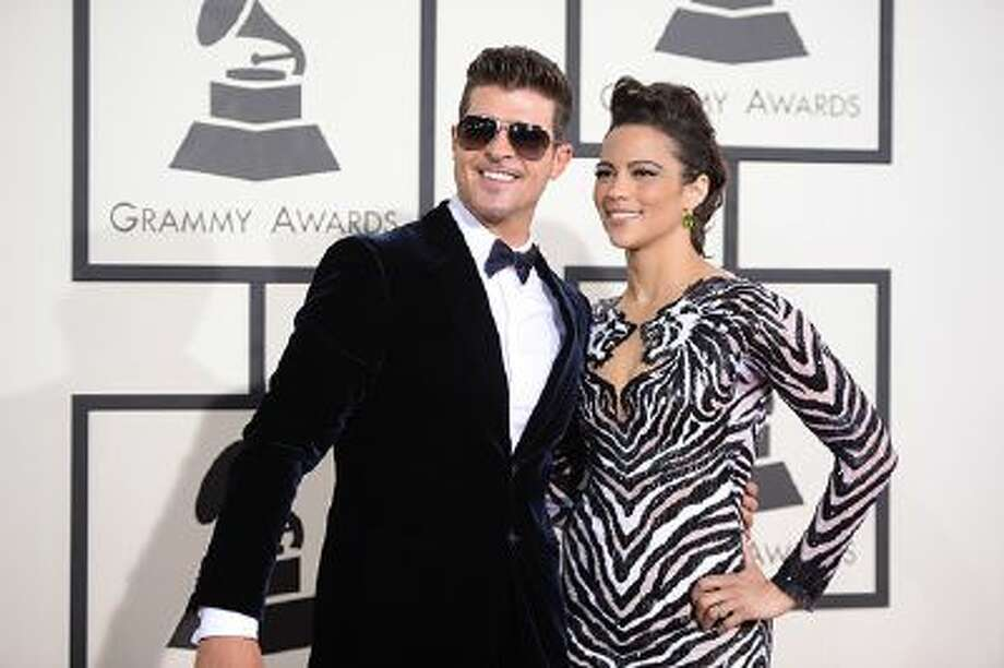 """Nominee For Best Pop Vocal Album for """"Blurred Lines"""" Robin Thicke (L) and actress Paula Patton arrive on the red carpet for the 56th Grammy Awards at the Staples Center in Los Angeles, California, January 26, 2014. AFP PHOTO ROBYN BECK        (Photo credit should read ROBYN BECK/AFP/Getty Images) Photo: AFP/Getty Images / 2014 AFP"""
