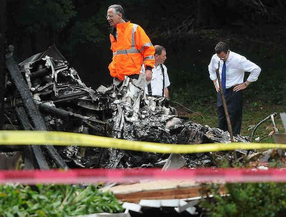 East Haven Mayor Joseph Maturo, left, East Haven Fire Chief Doug Jackson, center, and Gov. Dannel P. Malloy, right, in the backyard at the scene of a plane crash that hit two houses at 64 and 68 Charter Oak Ave. between James and Gordon streets in East Haven Friday afternoon. Peter Hvizdak/Register Photo: New Haven Register / ©Peter Hvizdak /  New Haven Register