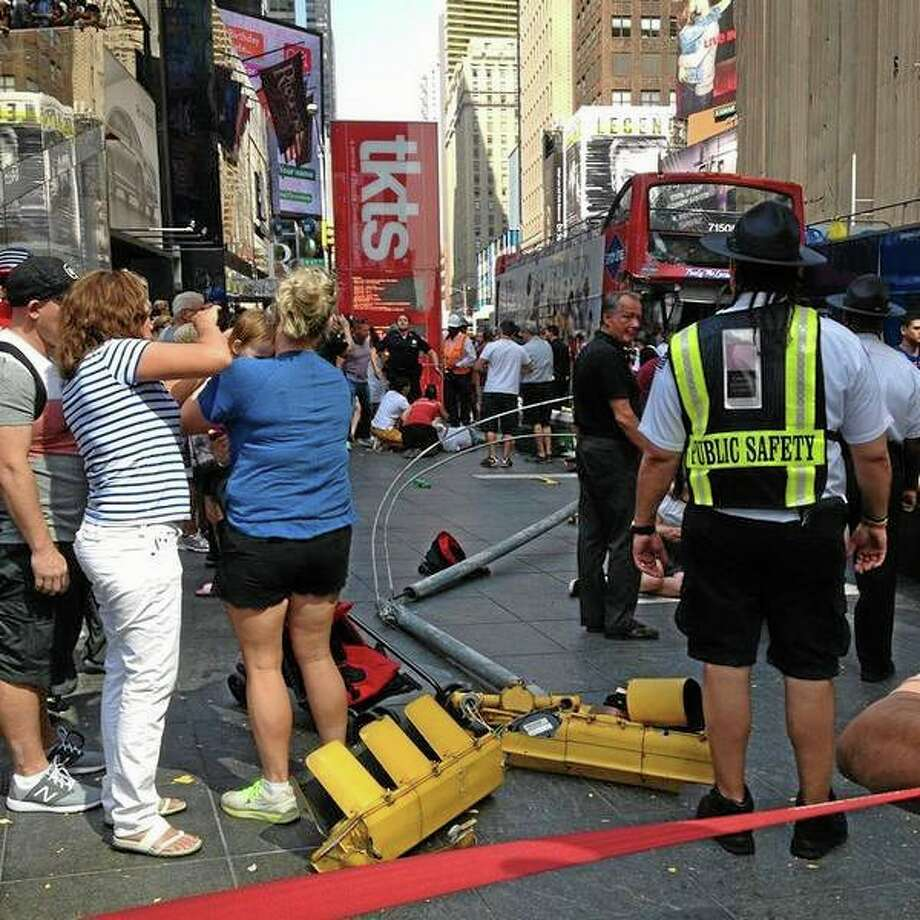 In this photo provided by Josh Price, pedestrians gather at the scene of a bus crash as first responders attend to the victims, Tuesday, Aug. 5, 2014, in New York Cityís Times Square. The Theater District collision of two double-decker tour buses injured more than a dozen people. (AP Photo/Josh Price) Photo: AP / Josh Price