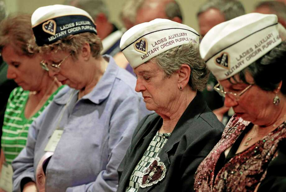 Attendees pray during the invocation at the opening of the National Order of the Purple Heart National Convention in Denver, Tuesday, Aug. 5, 2014. U.S. Veterans Administration Deputy Secretary Sloan Gibson says more employees will be disciplined as the department sorts out a scandal over long waits for health care and falsified data. (AP Photo/Brennan Linsley) Photo: AP / AP