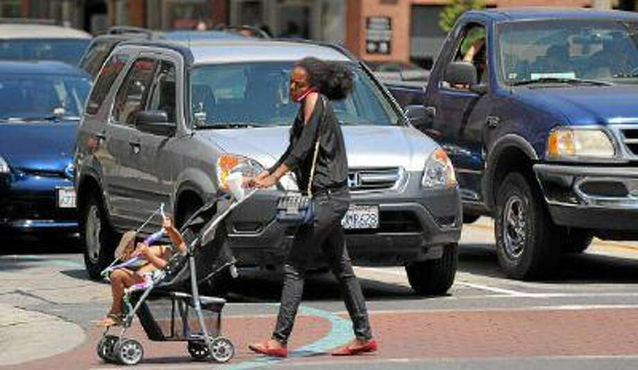 A lady talks on the phone while pushing a stroller across Colorado Blvd at Fair Oaks Ave. The U.S. Department of Transportation said the number of pedestrian deaths has been on the rise in the last two years.