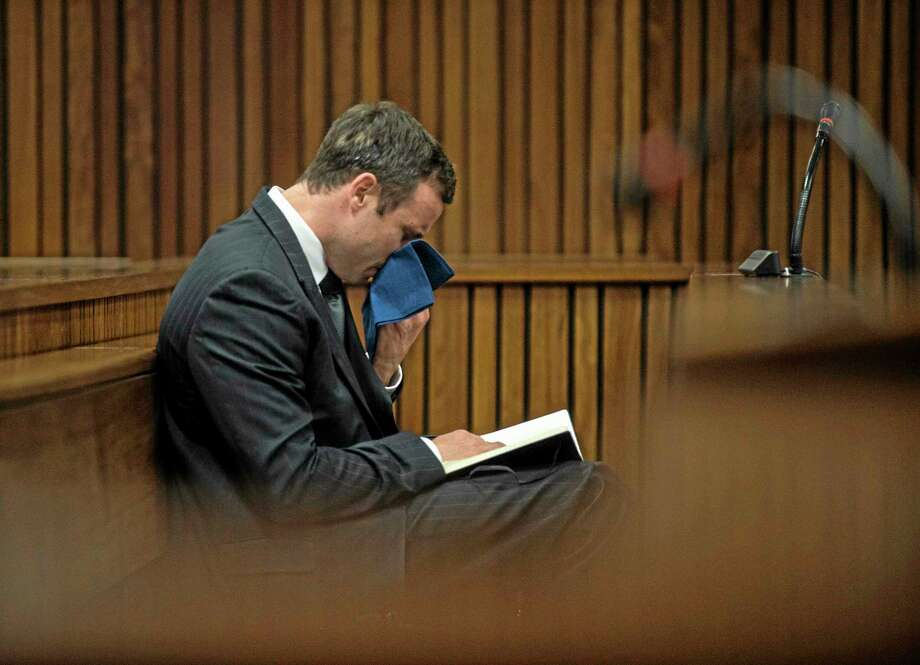 Oscar Pistorius reacts as he listens to the state prosecutor summarizing evidence at his murder trial in Pretoria, South Africa, Thursday, Aug. 7, 2014. The chief prosecutor said Thursday the double-amputee athlete's lawyers have floated more than one theory in a dishonest attempt to defend against a murder charge for his killing of girlfriend Reeva Steenkamp.  (AP Photo/Mujahid Safodien, Pool) Photo: AP / POOL AFP