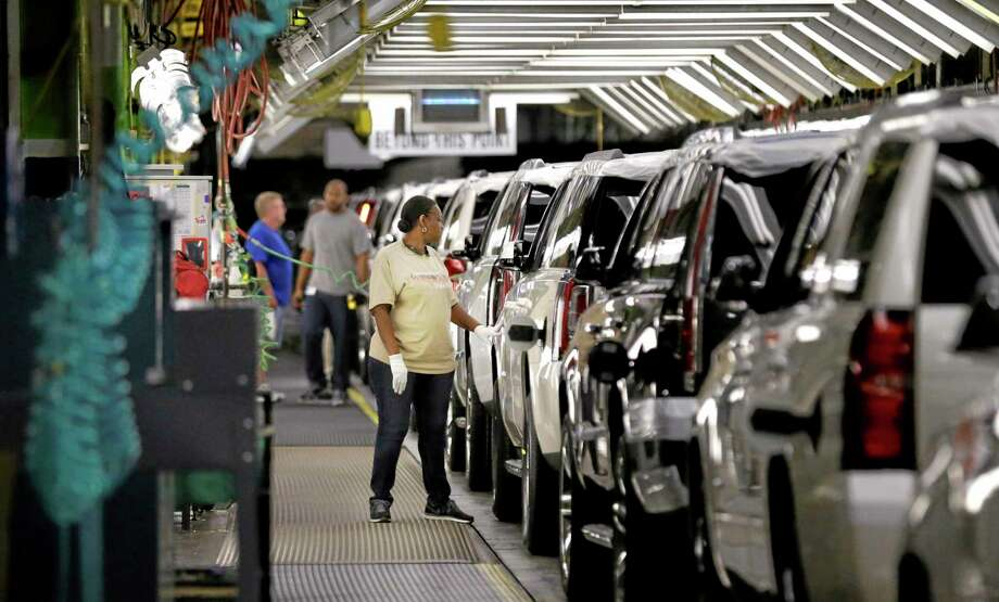 An auto worker inspects finished SUVs coming off the assembly line at the General Motors auto plant in Arlington, Texas. Photo: LM Otero — The Associated Press File Photo  / AP