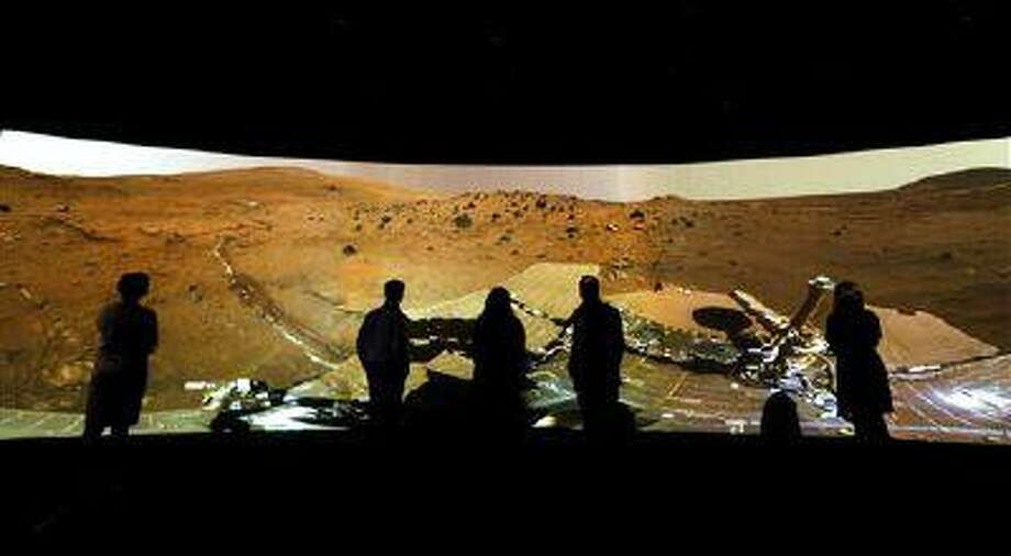 """FILE - In this Wednesday, June 5, 2013 file photo, people look at the """"Mars Window,"""" a projection of images taken by NASA's Mars Curiosity Rover at the Visions of the Universe exhibition at The National Maritime Museum in Greenwich, London. (AP Photo/Kirsty Wigglesworth) Photo: AP / AP"""