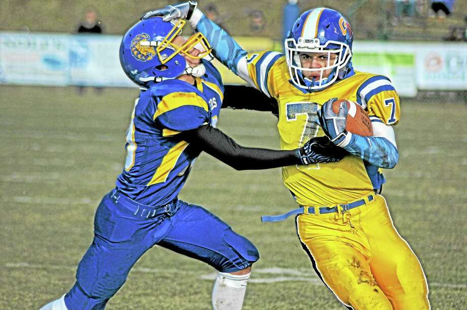 Gilbert/Northwestern running back Tony Ortiz stiff-arms a Housatonic/Wamogo defender on his way to a big gain during a game last month. Photo: Sean Meenaghan — Register Citizen