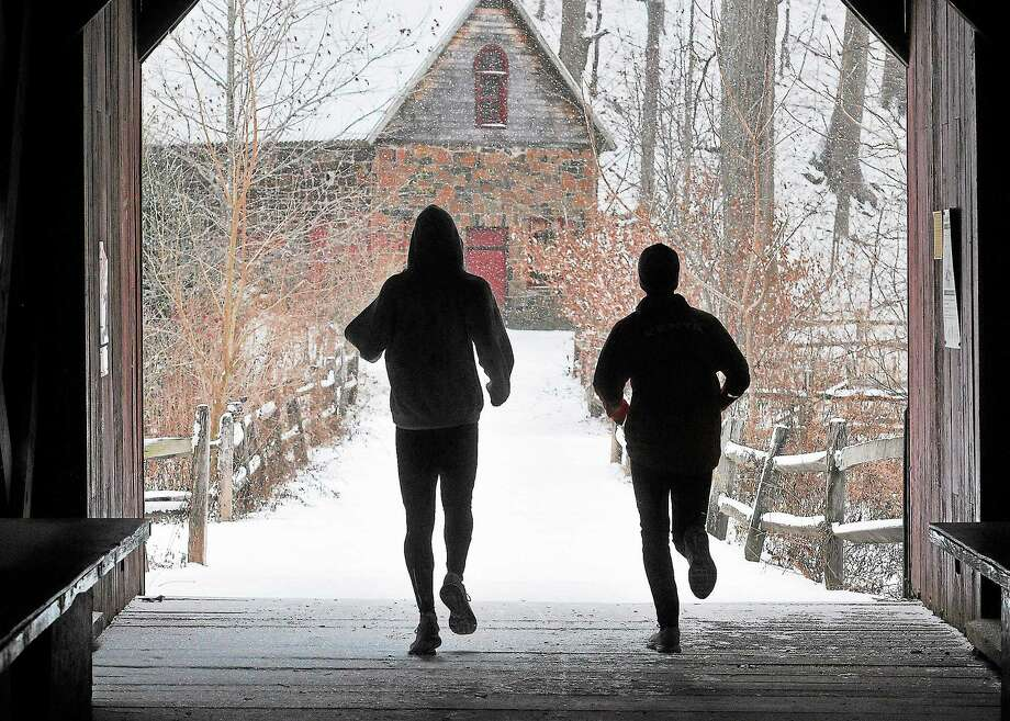 Runners make their way through the covered bridge at the Eli Whitney Museum during Saturday's snowfall in New Haven. Photo: Peter Casolino — New Haven Register