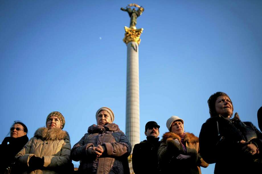 """Ukrainians sing attend commemorations for writer and Ukrainian nationalist Taras Shevchenko in Kiev's Independence Square, Ukraine, Sunday, March 9, 2014. As separatists in Crimea kept up pressure for unification with Moscow, Ukraine solemnly commemorated the 200th anniversary of the birth of its greatest poet, with the prime minister vowing not to give up """"a single centimeter"""" of Ukrainian territory. (AP Photo/David Azia) Photo: AP / AP"""