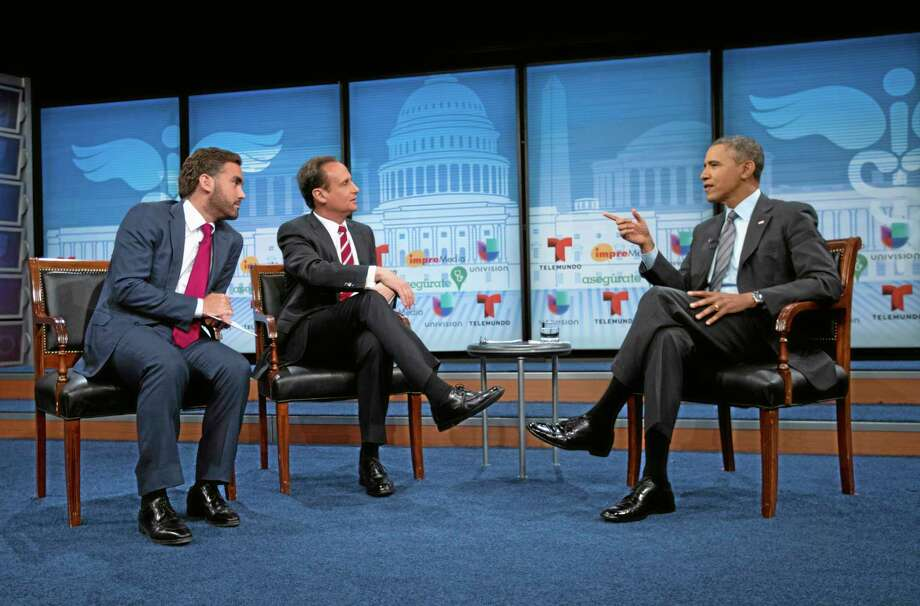 President Barack Obama talks with television hosts Jose Diaz Balart, center, and Enrique Acevedo, left, during a town hall event on the importance of the benefits of the Affordable Care Act for Hispanic community, Thursday, March 6, 2014, at the Newseum in Washington. (AP Photo/Pablo Martinez Monsivais) Photo: AP / AP