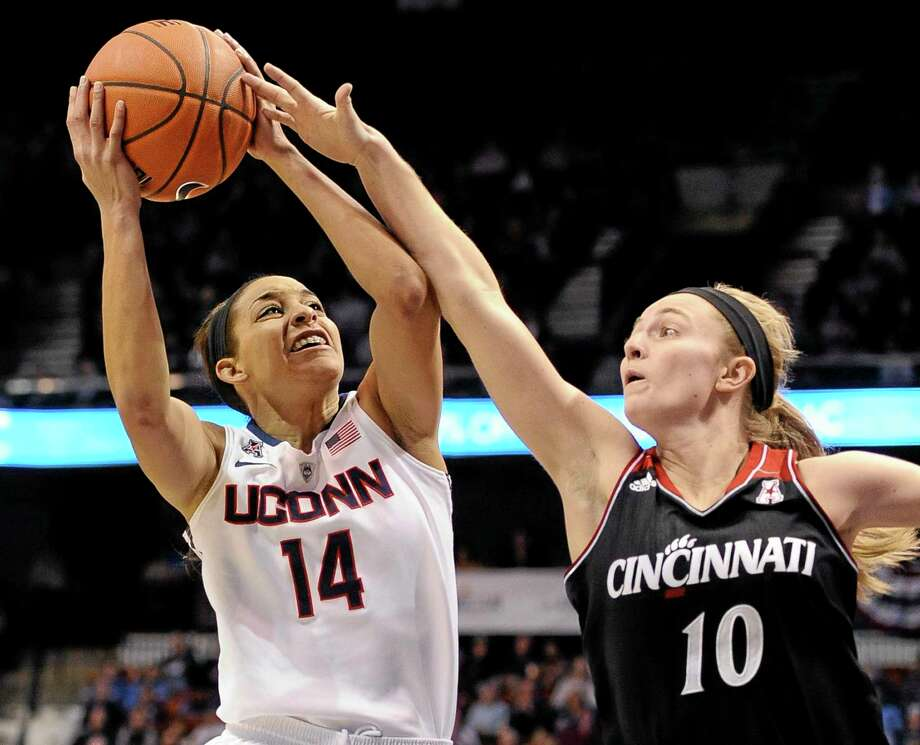 Cincinnati's Kayla Cook, right, fouls UConn's Bria Hartley during the first half of the Huskies' 72-42 win in the quarterfinals of the American Athletic Conference tournament on Saturday in Uncasville. Photo: Jessica Hill — The Associated Press  / FR125654 AP