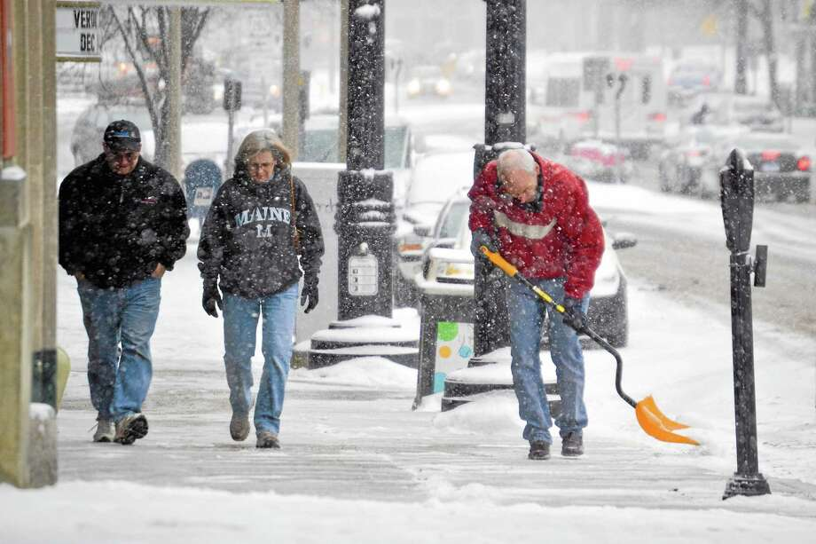 A man shovels a sidewalk along Torrington's Main Street early Saturday afternoon during the start of a storm that dropped a total of 7.5 inches on the city by Sunday morning. Photo: Tom Caprood—Register Citizen
